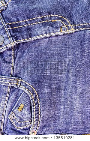 Fragment of the old worn blue denim with a horizontal seam