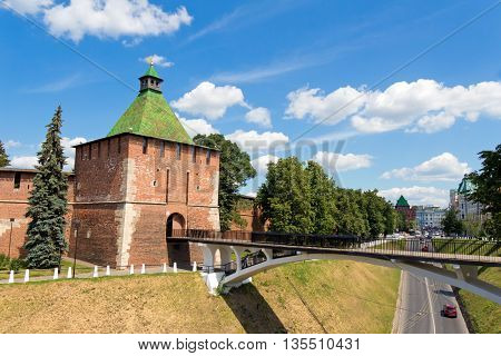 Nikol'skaya tower (Nicholas) the Kremlin Nizhegorodskiy district Nizhny Novgorod Russia. Tower and wall of red brick. A tourist attraction. The building is old. Standing on the hill. Pedestrian bridge (white) to the other side of the ravine.