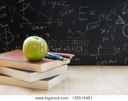 Education element book pencil green apple on desktop and back to school background.