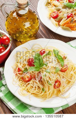 Spaghetti and penne pasta with tomatoes and basil on wooden table