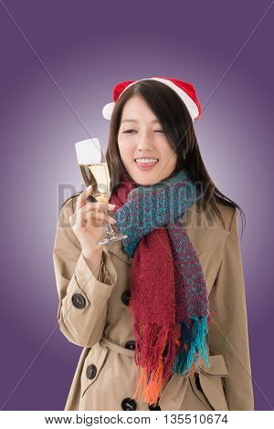 Smiling Asian woman hold a glass of champagne and look at you in a Christmas party, closeup portrait