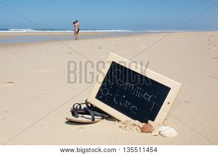Summer time chalkboard on a beach background