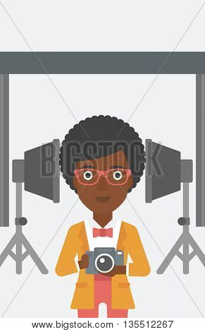 An african-american woman holding a camera on the background of photo studio with lighting equipment vector flat design illustration. Vertical layout.