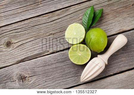 Fresh ripe limes and juicer on wooden table. Top view with copy space