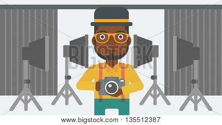 An african-american man holding a camera on the background of photo studio with lighting equipment vector flat design illustration. Horizontal layout.