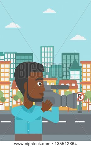 An african-american cameraman with video camera taking a video on a city background vector flat design illustration. Vertical layout.