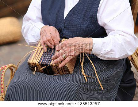 Senior Woman While Creating A Straw Bag