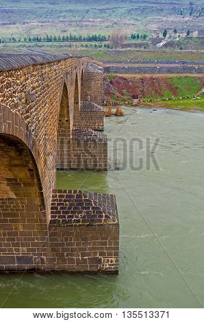 The scenic arch bridge named Dicle or Silvan connects two banks of the Tigris River Diyarbakir Turkey.
