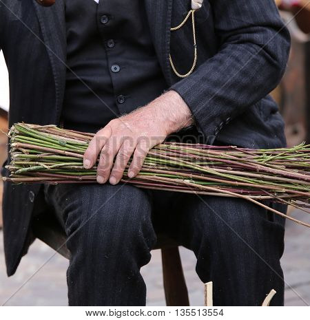 Senior Man With A Big Hand Tightens The Bundle Of Sticks