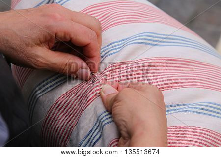 Woman While Sewing With Needle And Thread The Pillow