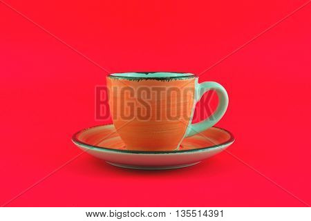 Orange cup and saucer on red background
