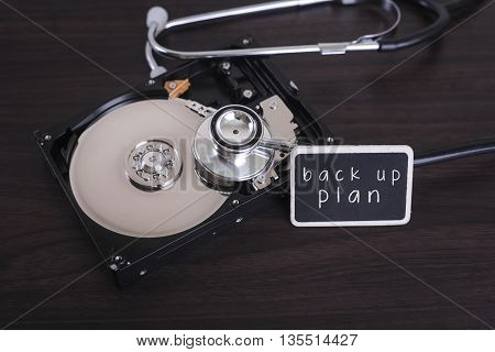 A stethoscope scanning for lost information on a hard drive disc with back up plan word on board
