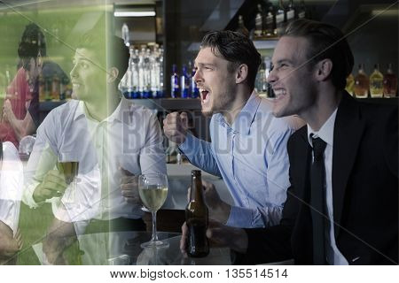 Handsome friends having a drink together against rugby players tackling during game