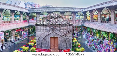 ANKARA TURKEY - JANUARY 16 2015: The old building of Suluhan Inn medieval Caravan Saray with the large courtyard nowadays includes outdoor cafe and the stalls with artificial flowers on January 16 in Ankara.
