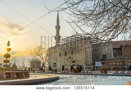 ANKARA TURKEY - JANUARY 16 2015: The scenic winter sunset over the Haci Bayram Square with the beautiful frozen pond ancient Temple wall and high minaret on January 16 in Ankara.