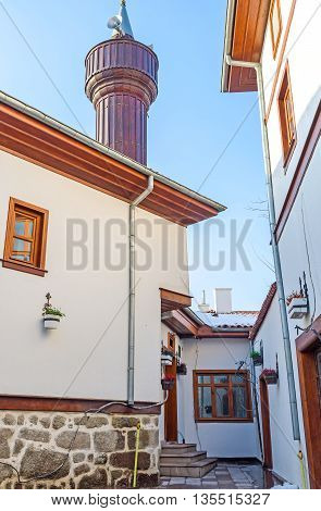 The new wooden minaret rises over the white cottages in the restored neighborhood of the Turkish village Ankara Turkey.