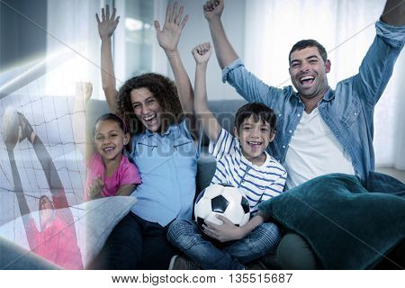 Composite image of family watching sport match on television and raising arms at home