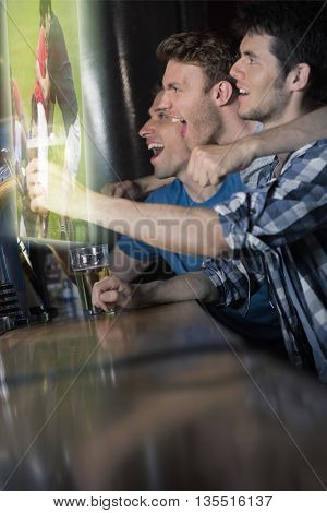 Composite image of friends are watching sport on television in a pub