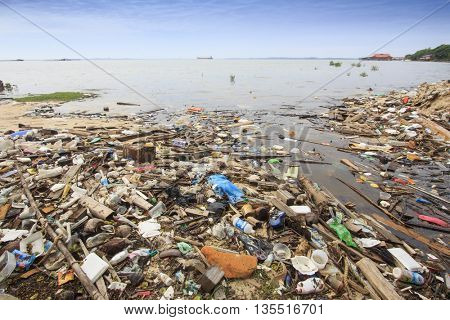 SANDAKAN, MALAYSIA - 23 JUNE 2016: Pollution environmental problem. Plastic bags and bottles on beach beside ocean due to no recycling or refuse disposal.