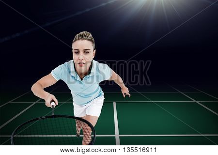 Pretty blonde playing badminton against view of a badminton field