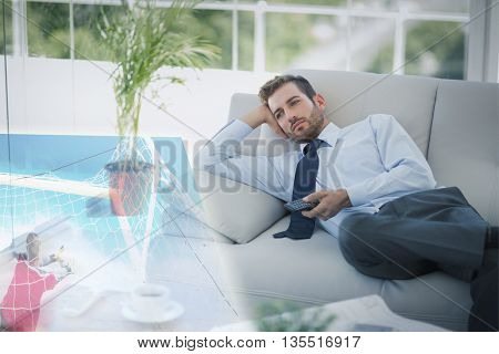 Composite image of businessman is watching sport on television at home