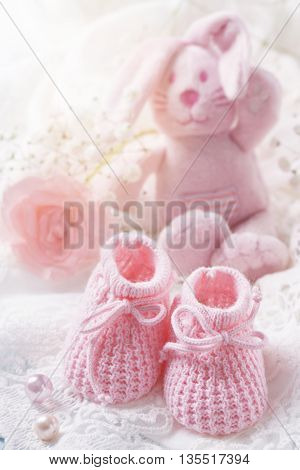 Pink baby shoes on a white fabric