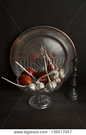 still life with garlic and tomatoes with moody light
