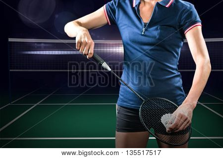 Badminton player holding a racket ready to serve against view of a badminton field
