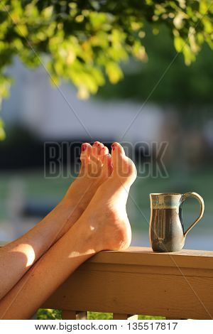 Woman's feet resting on porch railing on a beautiful summer evening just before dusk.