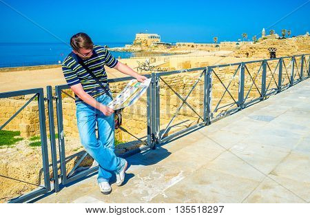 CAESARIA ISRAEL - MAY 19 2016: The young man explores the map and chooses the interesting tourist route on May 19 in Caesaria.