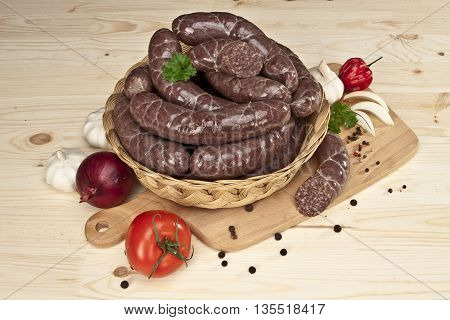 composition of blood sausage in basket on a woden board, with garlic, onion, pepper, tomato and herbal