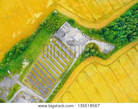 Aerial view to solar power plant in wheat field. Industrial background on renewable resources theme.