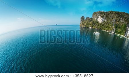 Aerial view of the sea with rocky island and anchored yacht in the bay. Thailand