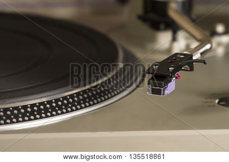 A retro turntable close-up with a needle