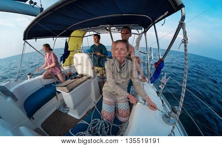 Group of young friends sailing in a open blue sea
