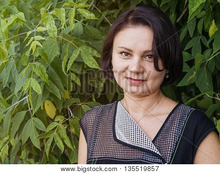 Outdoor portrait of an adult woman against a background of foliage