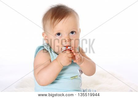 close-up, little child in blue T-shirt looks up and chews nipple white background
