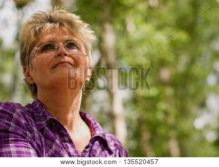 Portrait of a pensive elderly woman with trees in the background.