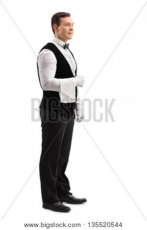 Full length portrait of a young male waiter holding a towel isolated on white background