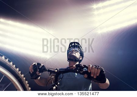 Composite image of man cycling with mountain bike against spotlight