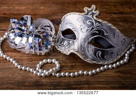 mask carnival white, black and gold on wood with pearl necklace and silver streamers