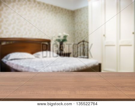 Wooden board empty table in front of blurred background. Perspective dark wood over blur in modern comfortable bedroom with dark brown wooden bed. Mock up for display or montage your products