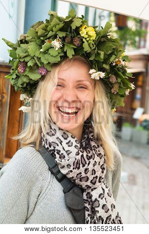 Portrait of the laughing girl in an oak wreath