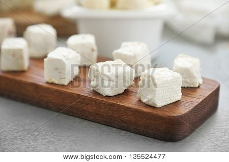 Sliced cheese on wooden cutting board