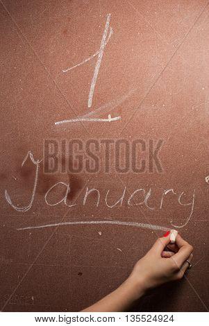 Female hand writes on the Board caption: 1 Jan