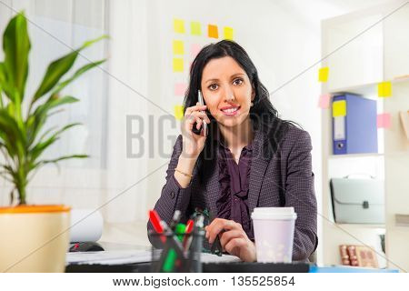 Cute businesswoman on phone in her office