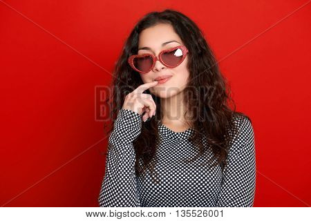 young woman beautiful portrait, posing on red background, long curly hair, sunglasses in heart shape, glamour concept