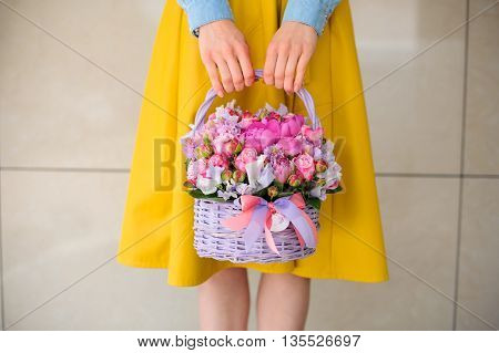 girl holding beautiful pink bouquet of mixed flowers in basket no face