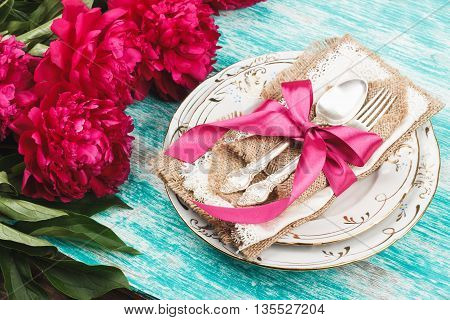 Table serving: Tableware with crimson peonies and silverware on the light blue background