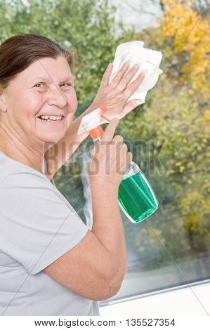 Smiling elderly woman washes a window with a liquid glass cleaner and cloth.